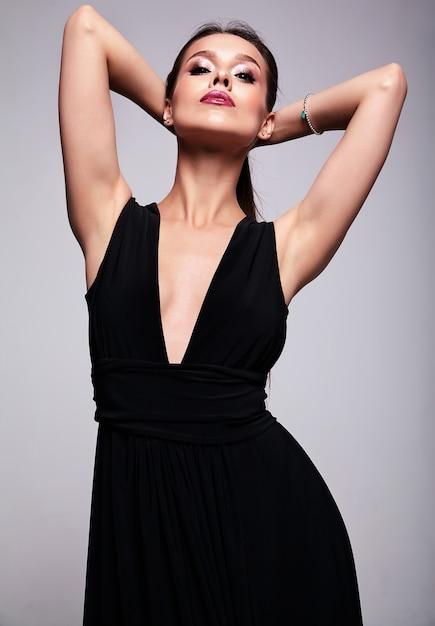 Ritratto di bello modello sorridente della donna del brunette in vestito nero con trucco di sera ed e labbra rosse isolate su gray Foto Gratuite