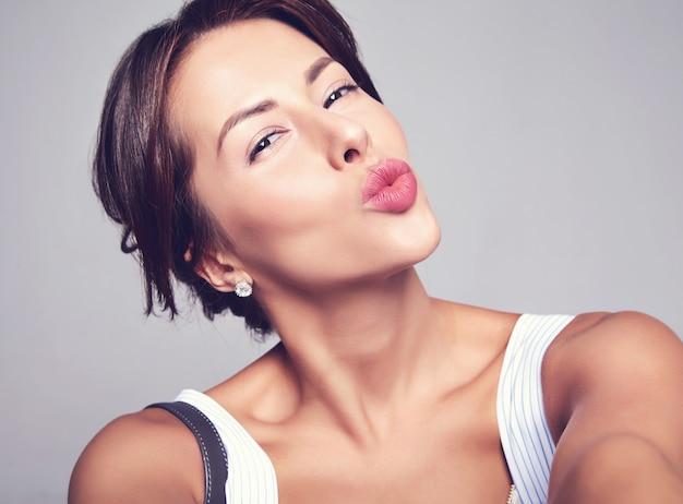 Ritratto di bello modello sveglio della donna del brunette in vestito casuale da estate senza trucco che fa la foto del selfie sul telefono isolato sul gray con la borsa. dare un bacio d'aria Foto Gratuite