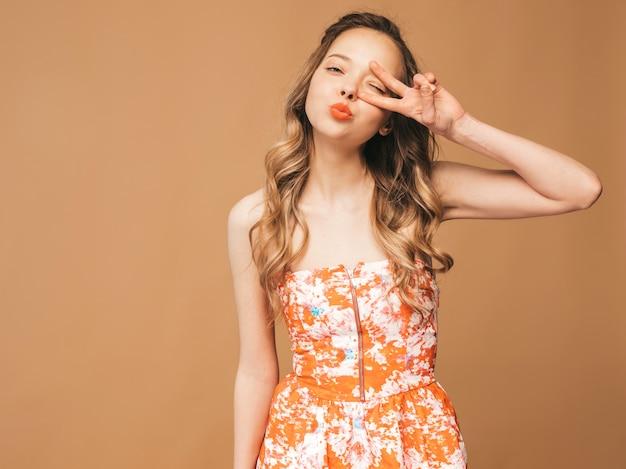Ritratto di bello modello sveglio sorridente con le labbra rosa. ragazza in abito colorato estivo. posa di modello mostrando segno di pace e dando bacio Foto Gratuite