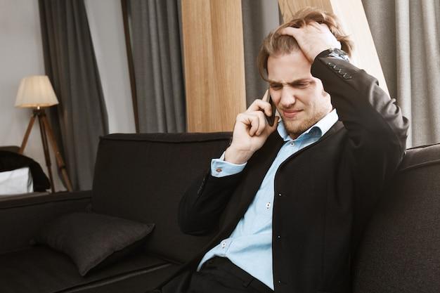 Ritratto di bello uomo barbuto infelice con capelli biondi che parla sul telefono e che è arrabbiato per i problemi di finanza in società. Foto Gratuite