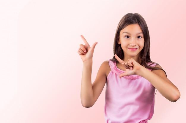 Ritratto di capelli scuri sorridenti felici della ragazza che indossano i vestiti rosa che indicano su con le sue dita Foto Premium