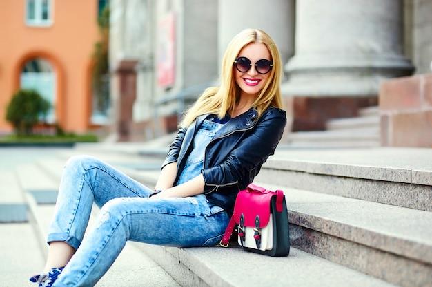 Ritratto di carino divertente moderno sexy urbano giovane elegante sorridente donna ragazza modello in luminoso moderno panno all'aperto seduto nel parco in jeans su una panchina in bicchieri con borsa rosa Foto Gratuite