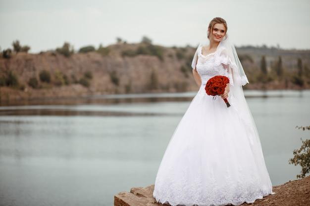 Ritratto di cerimonia nuziale di una bionda riccia carina con un bouquet. Foto Premium