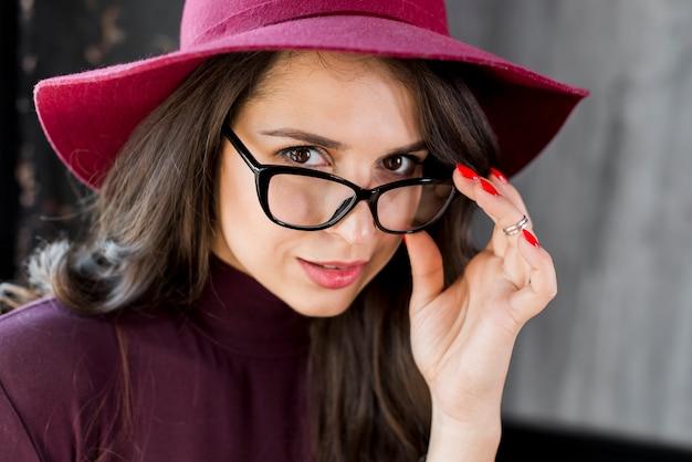 Ritratto di close-up di giovane bella donna alla moda con gli occhiali e cappello sopra la sua testa Foto Gratuite