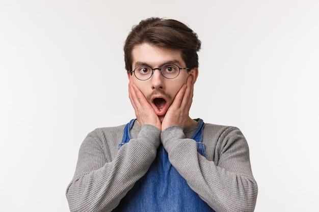 Ritratto di close-up scioccato e senza parole di un giovane dipendente maschio spettegolare sul collega, ascoltare incredibili notizie incredibili, tenere le mani sul viso, fissare la telecamera spaventato, Foto Premium