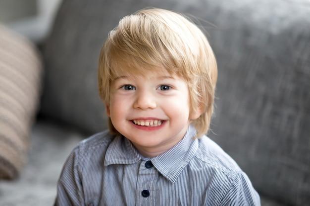 Ritratto di colpo in testa del ragazzo sveglio sorridente del bambino che guarda l'obbiettivo Foto Gratuite