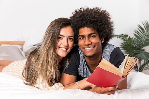Ritratto di coppia interrazziale leggendo insieme Foto Gratuite