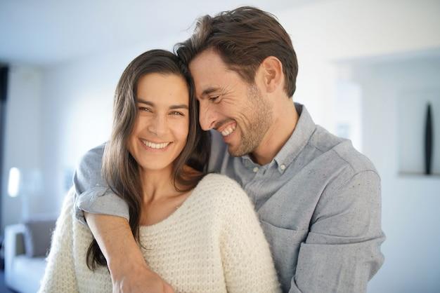 Ritratto di coppia splendida che abbraccia a casa Foto Premium