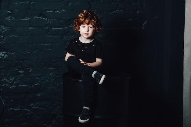 Ritratto di cute giovane ragazzo riccio in abiti casual scuri, seduto con le gambe incrociate Foto Premium