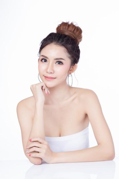 Ritratto di donna asiatica attraente seduto sorridente su sfondo bianco. Foto Premium