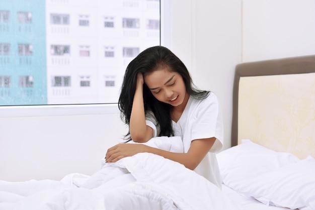 Ritratto di donna asiatica che si siede sul letto e soffre di mal di testa Foto Premium