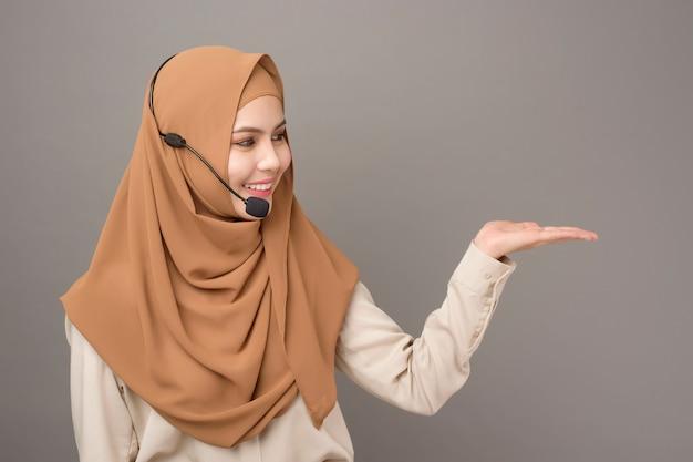 Ritratto di donna bella call center con hijab su grigio Foto Premium