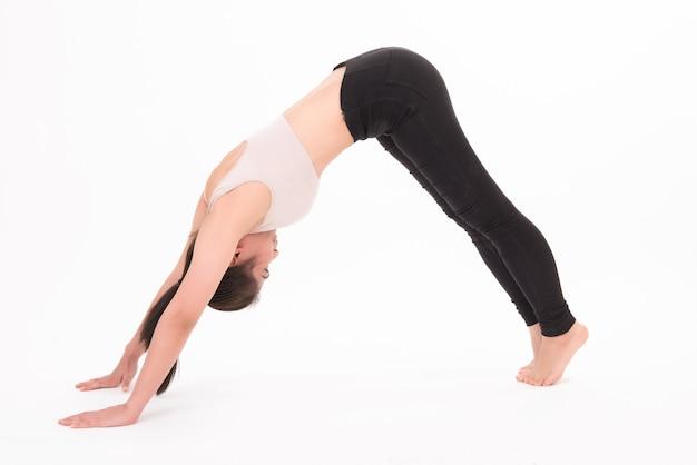 Ritratto di donna che allunga isolato su bianco. una ragazza che pratica yoga su bianco. Foto Premium