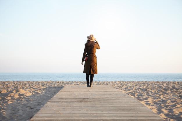 Ritratto di donna che cammina sul lungomare guardando il mare blu che indossa classico copricapo e cappotto marrone Foto Gratuite