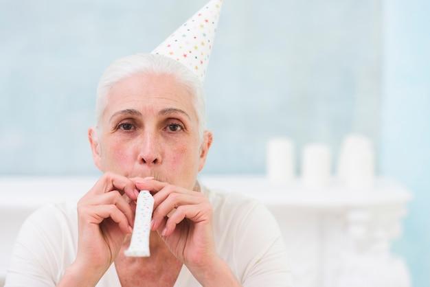 Ritratto di donna che soffia corno partito indossando il cappello di compleanno Foto Gratuite