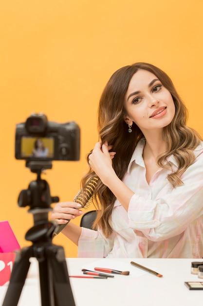 Ritratto di donna che spazzola i capelli sulla macchina fotografica Foto Gratuite