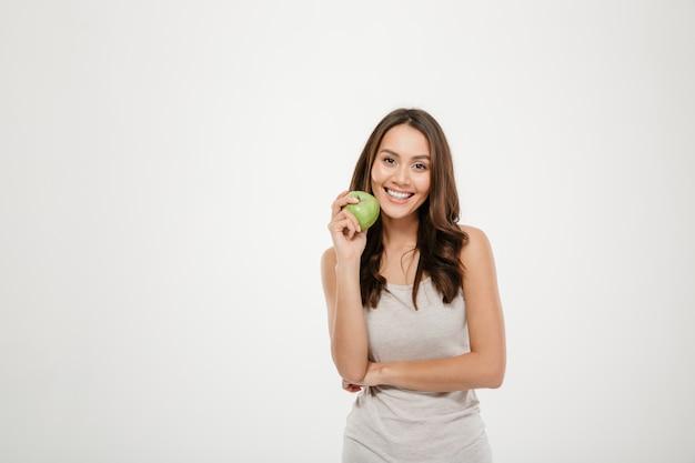 Ritratto di donna con lunghi capelli castani alla ricerca sulla fotocamera con mela verde in mano, isolato su bianco Foto Gratuite