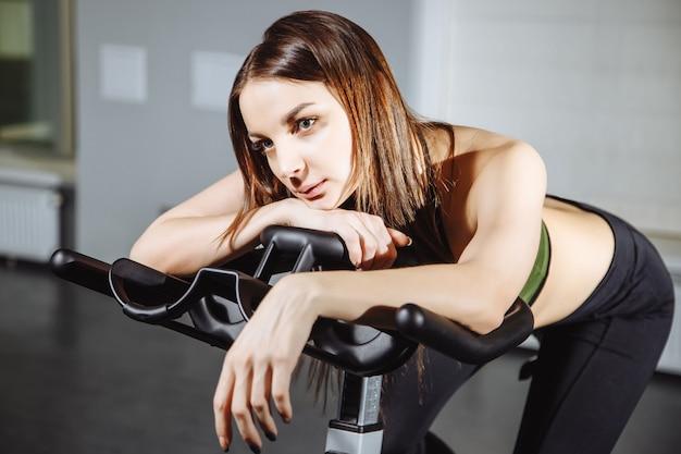 Ritratto di donna esausta che gira pedali sulla cyclette. Foto Premium