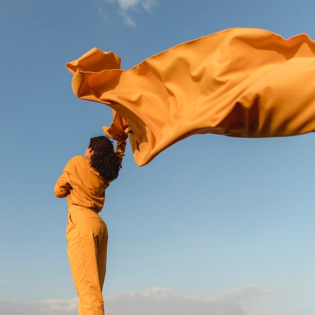 Ritratto di donna gioiosa con un panno giallo in natura Foto Gratuite