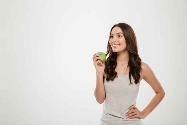 Ritratto di donna in buona salute con lunghi capelli castani in piedi isolato su bianco, degustazione di mela succosa verde Foto Gratuite