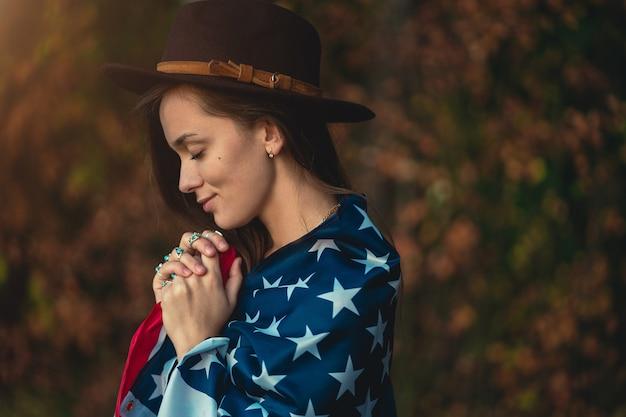 Ritratto di donna indie patriottica attraente in cappello con bandiera americana che indossa anelli d'argento con pietra turchese all'aperto. viaggia in america e celebra le vacanze del 4 luglio negli stati uniti Foto Premium