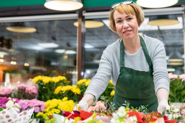 Ritratto di donna matura in posa con i fiori Foto Gratuite