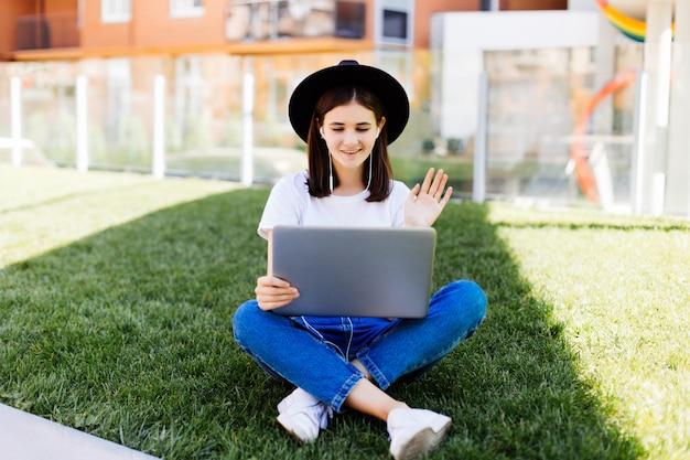 Ritratto di donna socievole che si siede sull'erba verde nel parco con le gambe incrociate durante il giorno d'estate durante l'utilizzo di laptop e auricolari wireless per la videochiamata Foto Gratuite