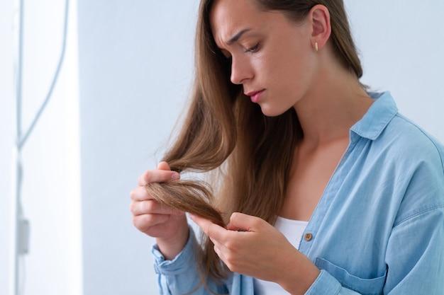Ritratto di donna triste infelice turbata con danneggiata ciocca di capelli che soffrono di capelli secchi e doppie punte. Foto Premium