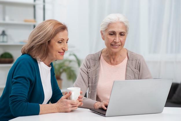 Ritratto di donne carine guardando un computer portatile Foto Gratuite