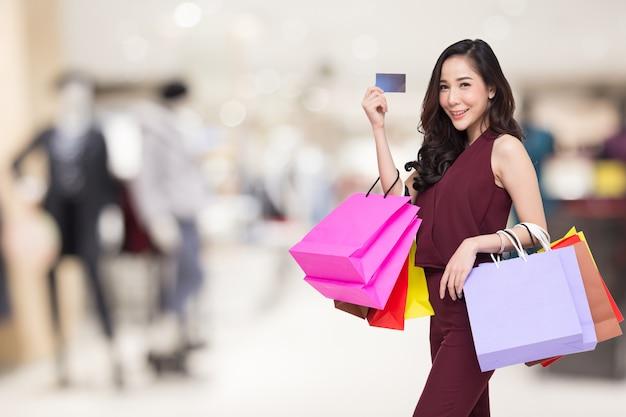 Ritratto di donne felici in vestito rosso che tiene i sacchetti della spesa e carta di credito Foto Premium