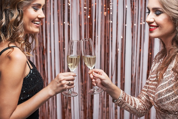 Ritratto di due belle donne eleganti tintinnio di bicchieri di champagne. Foto Premium