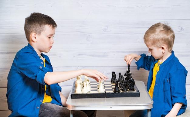 Ritratto di due bellissimi ragazzi in magliette gialle e giacche di jeans, camicie. i ragazzi stanno giocando a scacchi su un fondo di legno bianco. i fratellini giocano a scacchi. Foto Premium