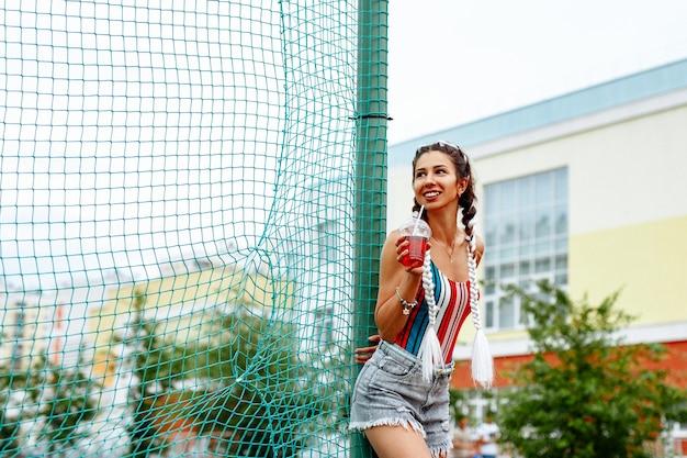 Ritratto di estate di una donna allegra con un drink rinfrescante sullo sfondo dello stadio. Foto Premium