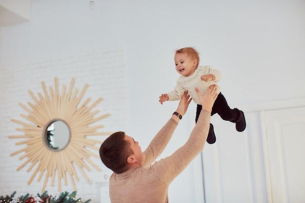 Ritratto di famiglia. il padre felice tiene la bambina felice in braccio in piedi nella stanza accogliente Foto Gratuite