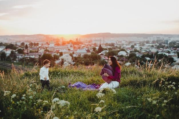 Ritratto di famiglia. natura. la mamma gioca con un cuscino per tenere il sole Foto Gratuite