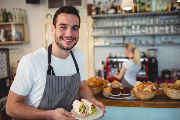 Ritratto di felice barista con panini freschi Foto Premium