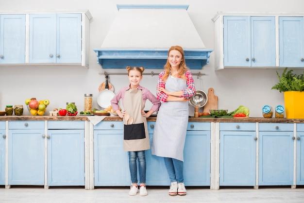 Ritratto di felice madre e figlia in grembiule in piedi in cucina Foto Gratuite