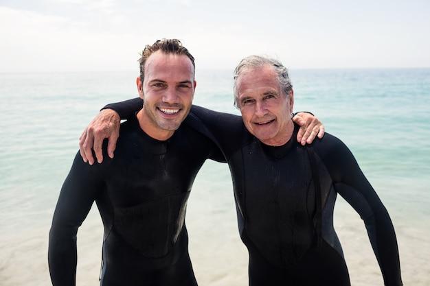 Ritratto di felice padre e figlio in muta abbracciando sulla spiaggia Foto Premium
