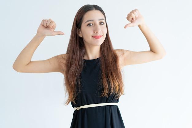 Ritratto di fiduciosa giovane imprenditrice che punta a se stessa Foto Gratuite