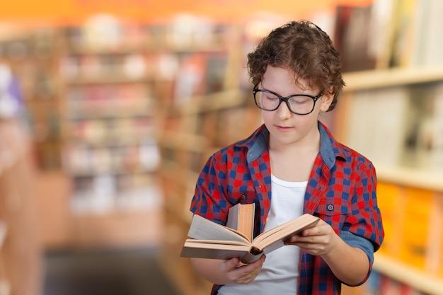 Ritratto di giovane attraente piccolo ragazzo di scuola allegro Foto Premium