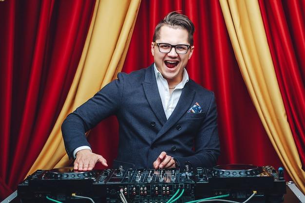 Ritratto di giovane bel carismatico dj in abito formale in piedi al mixer e sorridente. concetto di moda e discoteca Foto Premium