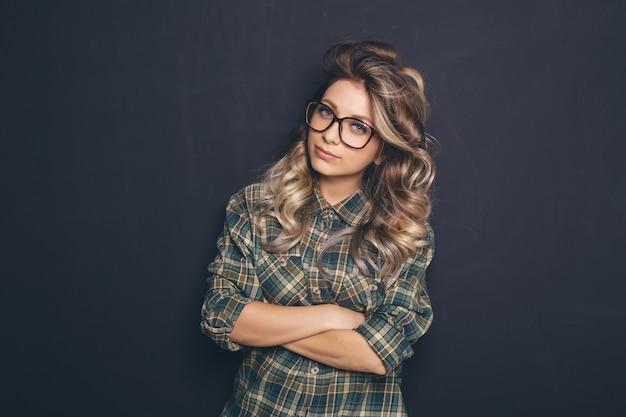 Ritratto di giovane bella bionda con gli occhiali alla moda e abbigliamento casual e in posa su sfondo nero Foto Gratuite