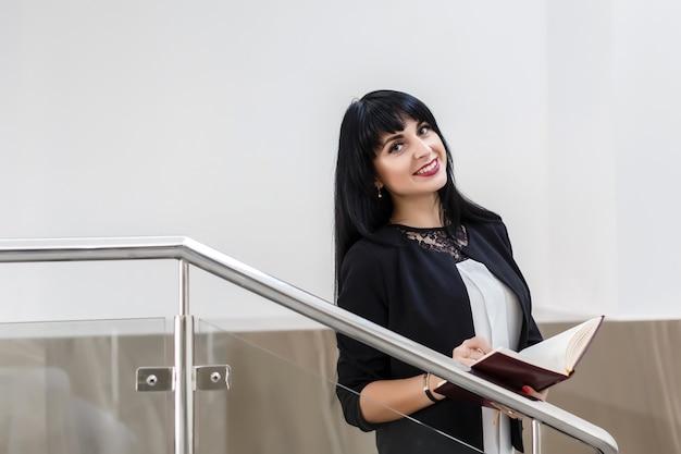 Ritratto di giovane bella donna bruna felice vestita in un tailleur nero, lavorando con un notebook, in piedi in ufficio, sorridente, guardando la fotocamera. Foto Premium