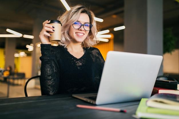 Ritratto di giovane bella donna seduta al tavolo in camicia nera, lavorando sul portatile in ufficio di co-working, con gli occhiali, sorridente, felice, positivo, bevendo caffè in tazza di carta Foto Gratuite