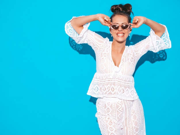 Ritratto di giovane bella donna sorridente sexy con acconciatura ghoul. ragazza alla moda in abiti casual bianco estate hipster vestito in occhiali da sole. modello a caldo isolato su blu Foto Gratuite
