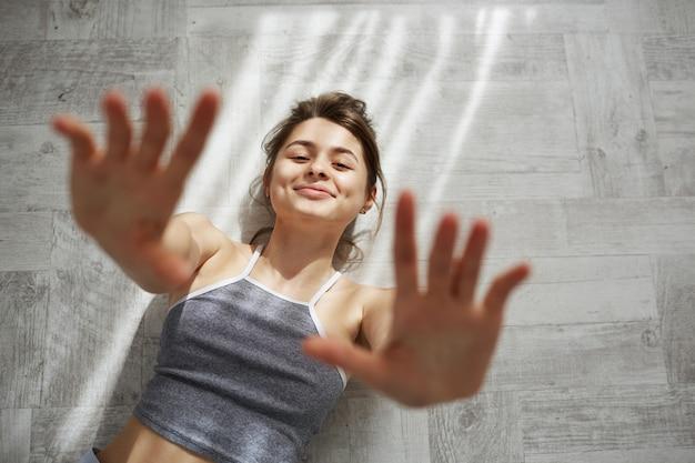 Ritratto di giovane bella donna tenera che sorride allungando le mani che si trovano sul pavimento nei sunlights di mattina. Foto Gratuite