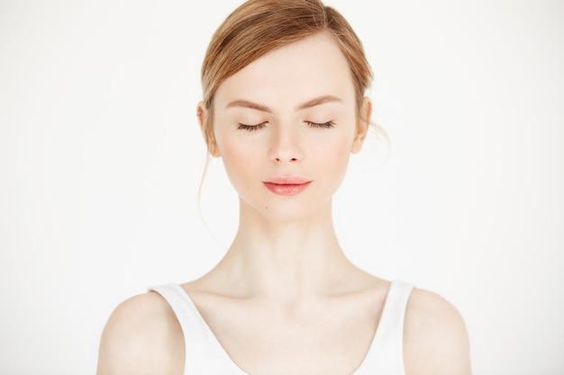 Ritratto di giovane bella ragazza con pelle fresca pulita isolata su fondo bianco. occhi chiusi. stile di vita di bellezza e salute. Foto Gratuite