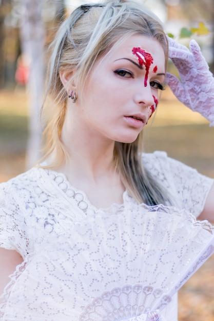 Ritratto di giovane bella ragazza con sangue halloween trucco sul suo viso Foto Premium