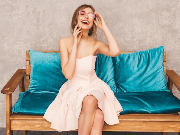 Ritratto di giovane bella ragazza sorridente in abito rosa chiaro estivo alla moda. donna spensierata sexy che si siede sul sofà blu luminoso. in posa in interni di lusso Foto Gratuite