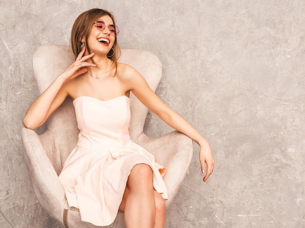 Ritratto di giovane bella ragazza sorridente in abito rosa chiaro estivo alla moda. donna spensierata sexy che si siede sulla sedia beige. in posa in interni di lusso Foto Gratuite